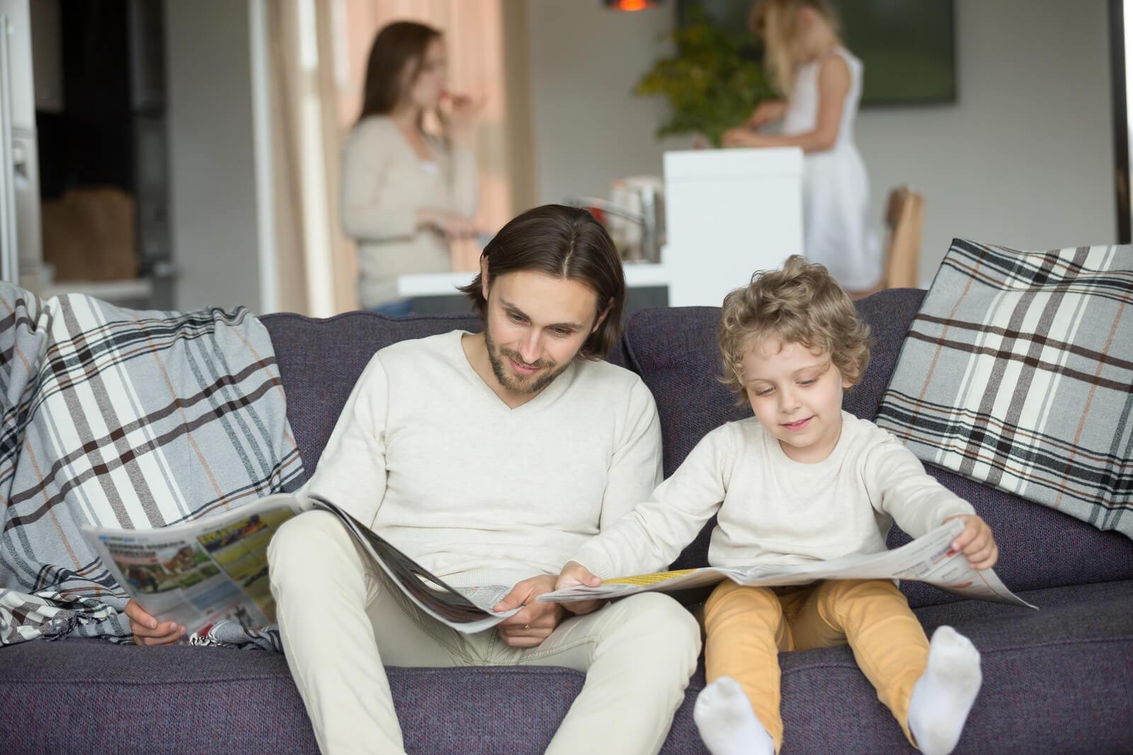 Padre e hijo leyendo el periódico como parte del aprendizaje observacional.