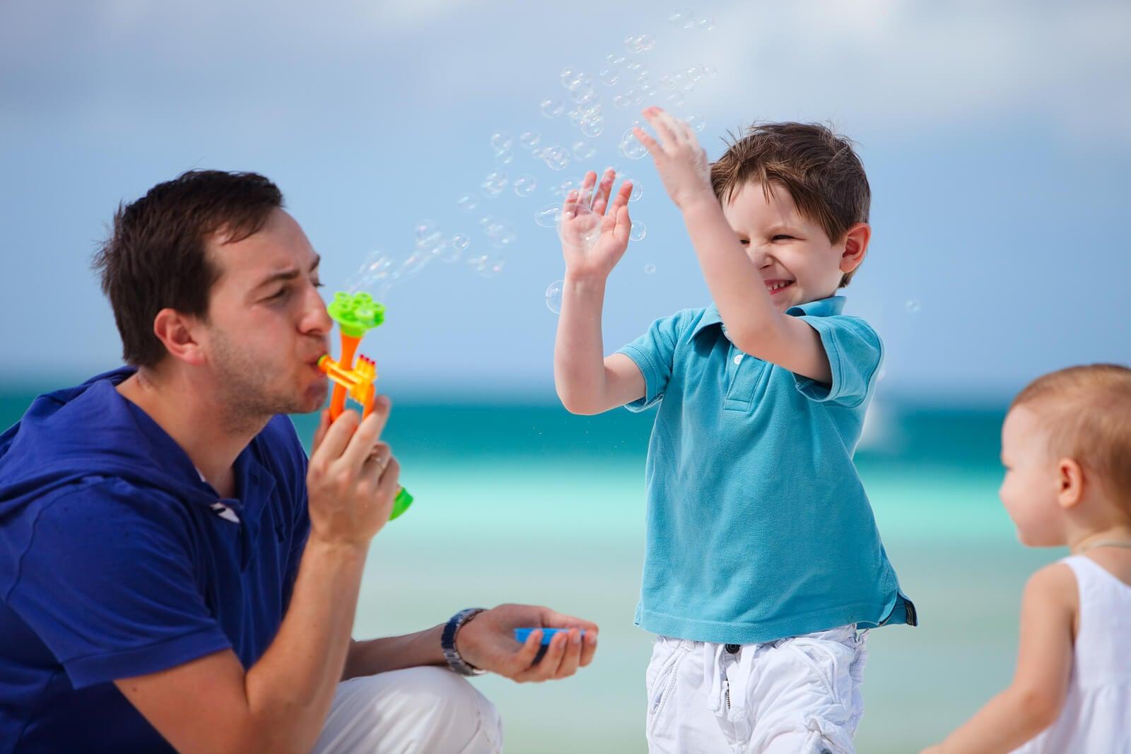 Padre jugando con sus hijos en la playa haciendo pompas de jabón.