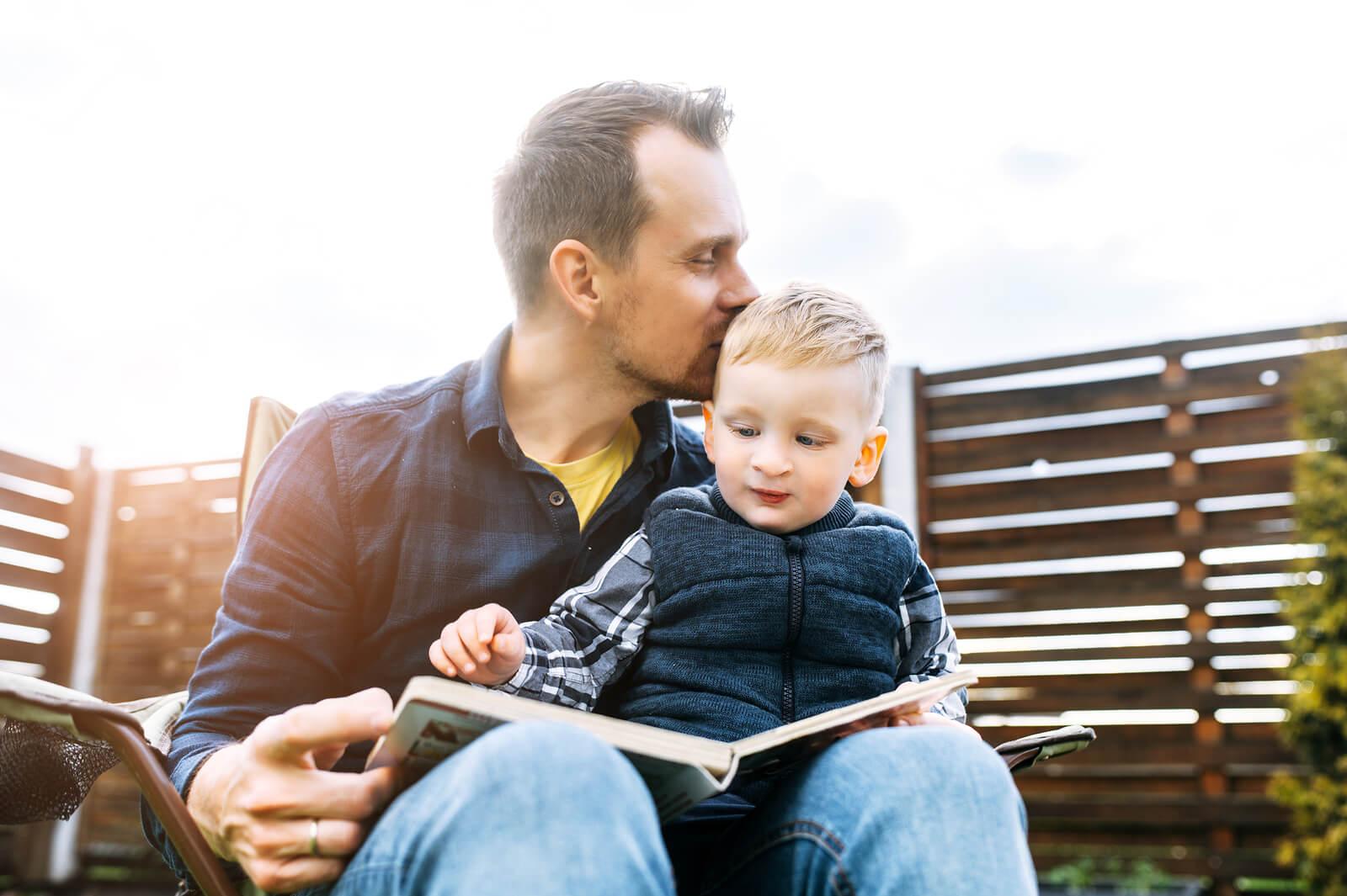 Padre dando un beso a su hijo en la cabeza mientras leen cuentos breves con valores.