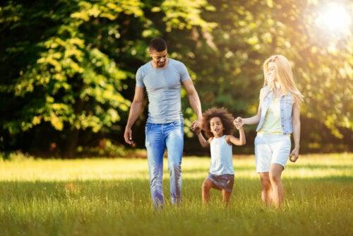 Padres dando un paseo con su hija por el campo cogidos de la mano.
