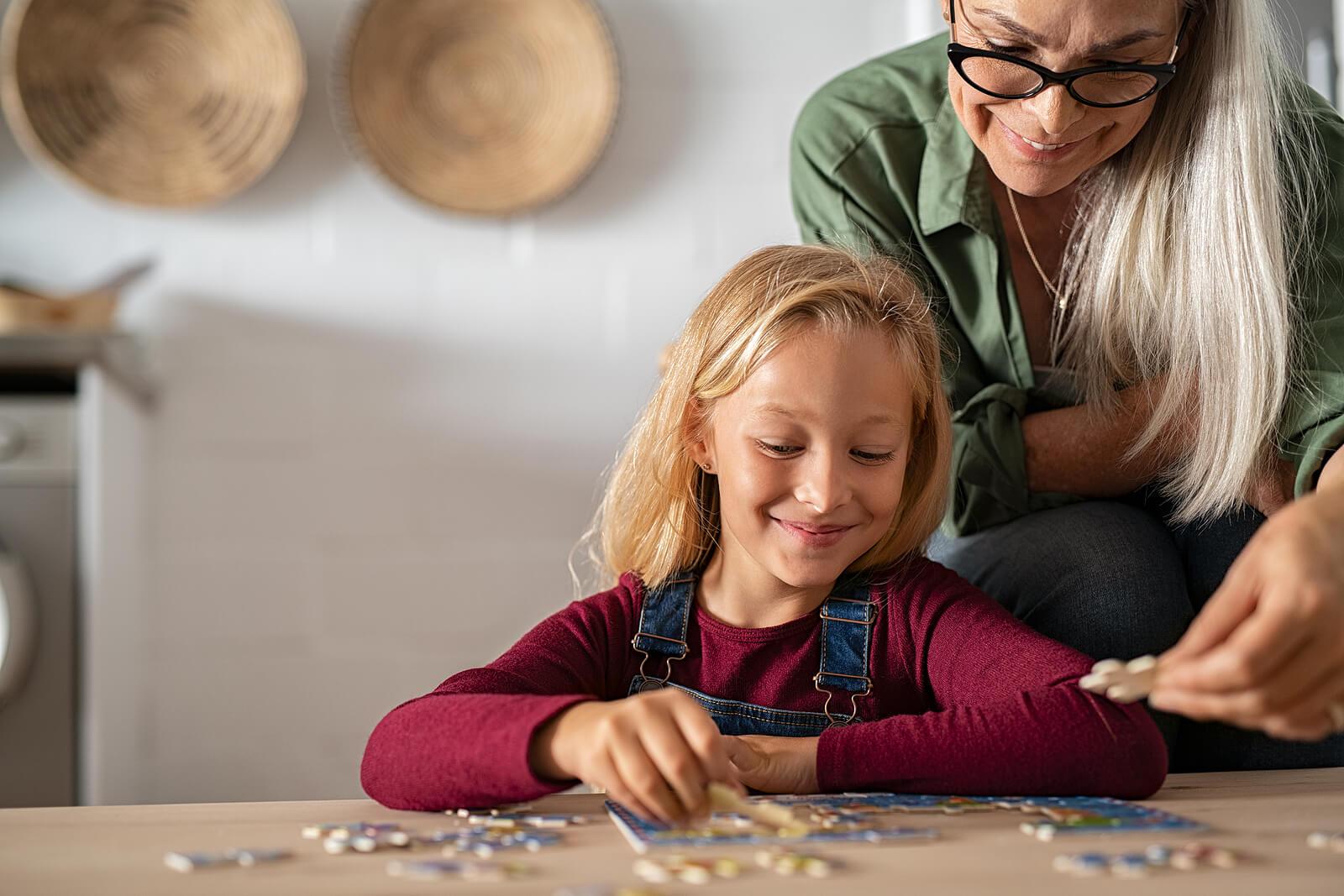 Abuela con su nieta haciendo puzzles para enseñarle a resolver problemas.