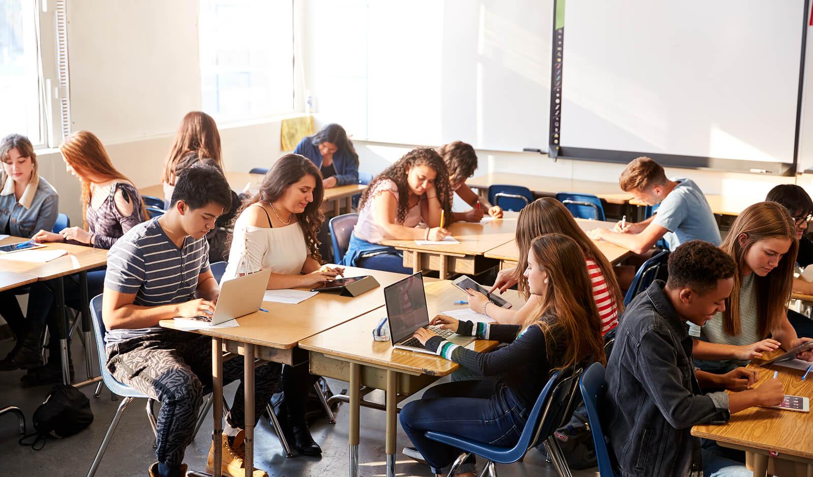 Alumnos en clase trabajando en grupo gracias a los métodos de educación nuevos.
