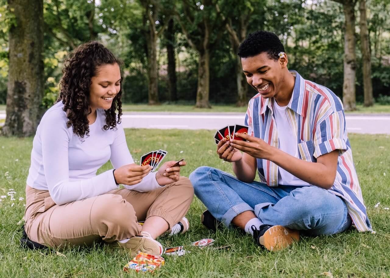 Amigos jugando al Uno, un juego de cartas, sentados en el césped.