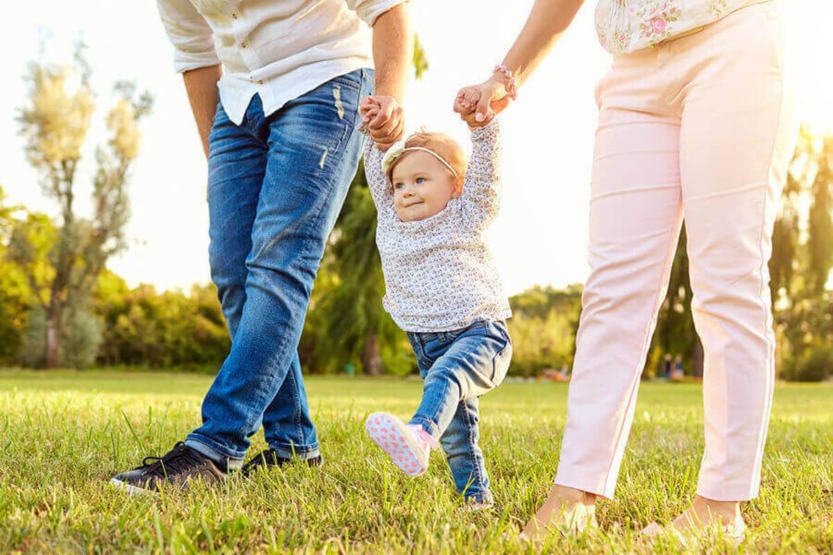 Bebé aprendiendo a caminar gracias a la ayuda de su padres con un apego parental seguro.