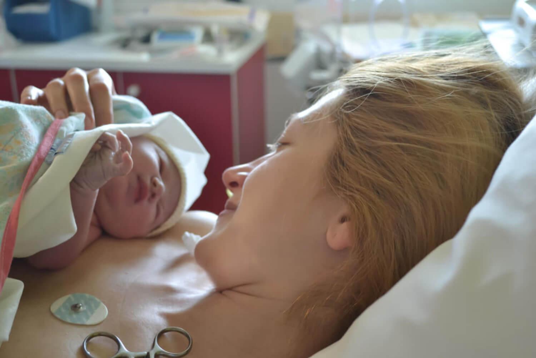 Madre con su bebé recién nacido en brazos tras sufrir sepsis neonatal.
