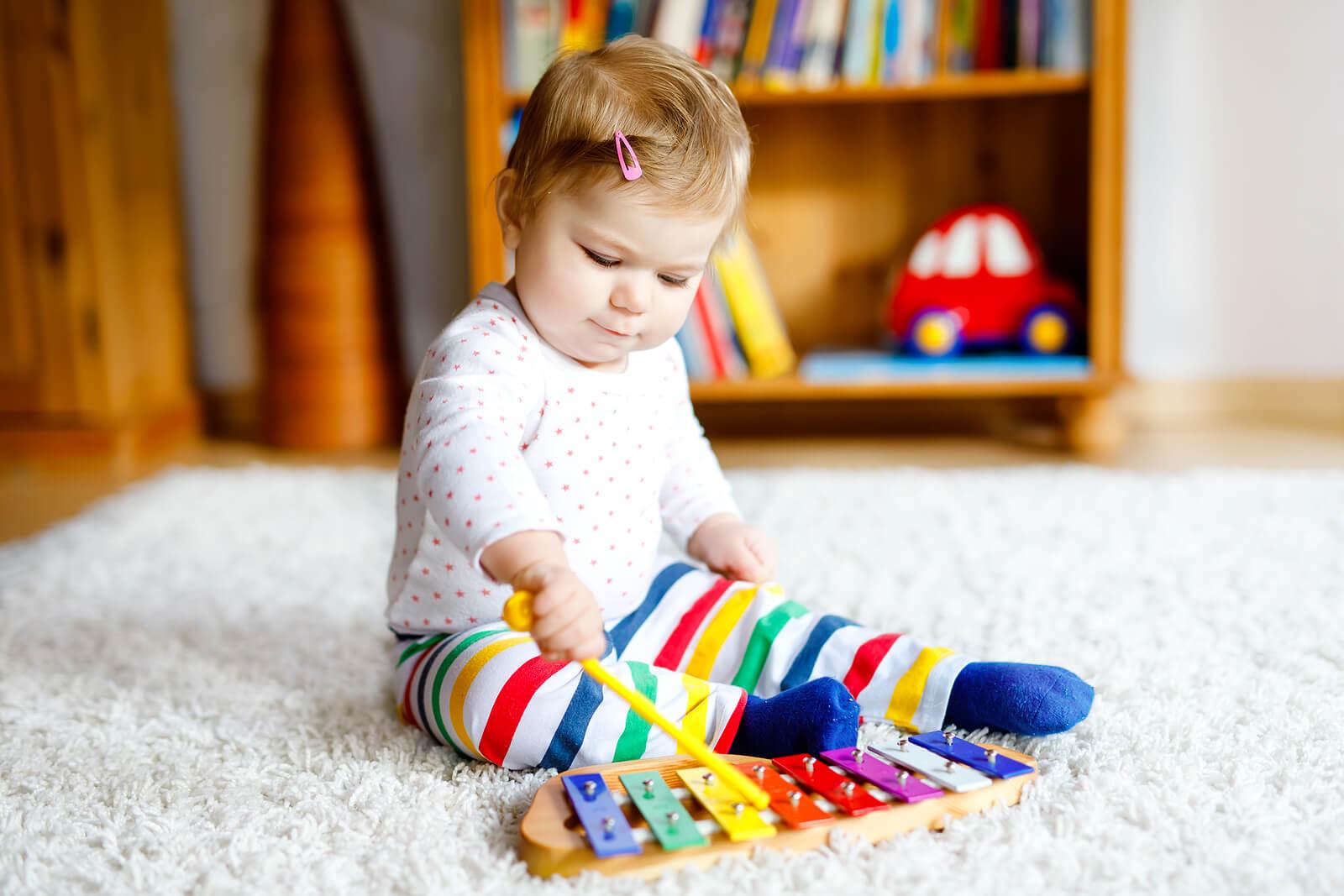 Bebé tocando un xilófono y haciendo música para potenciar el desarrollo integral infantil.
