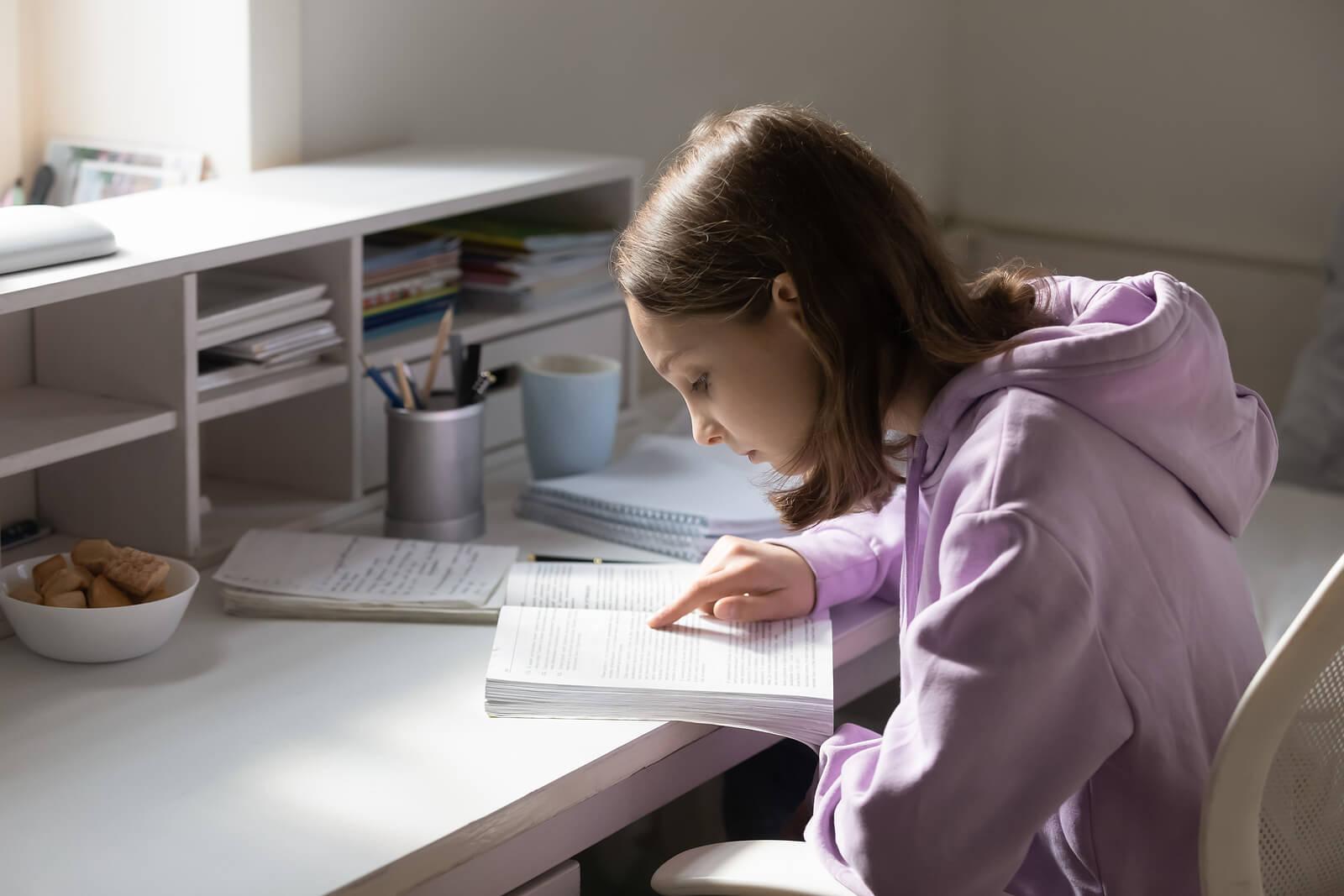 Chica adolescente en su cuarto estudiando.