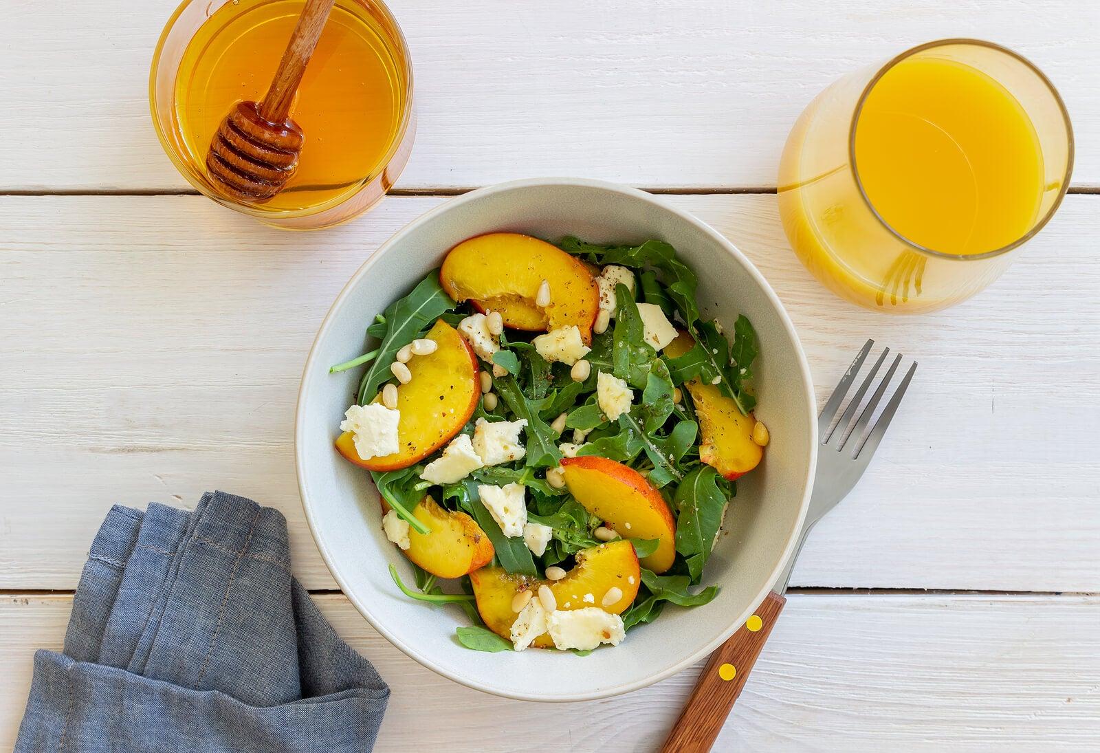 Ensalada de rúcula y melocotón, una de las recetas con fruta veraniega para niños.
