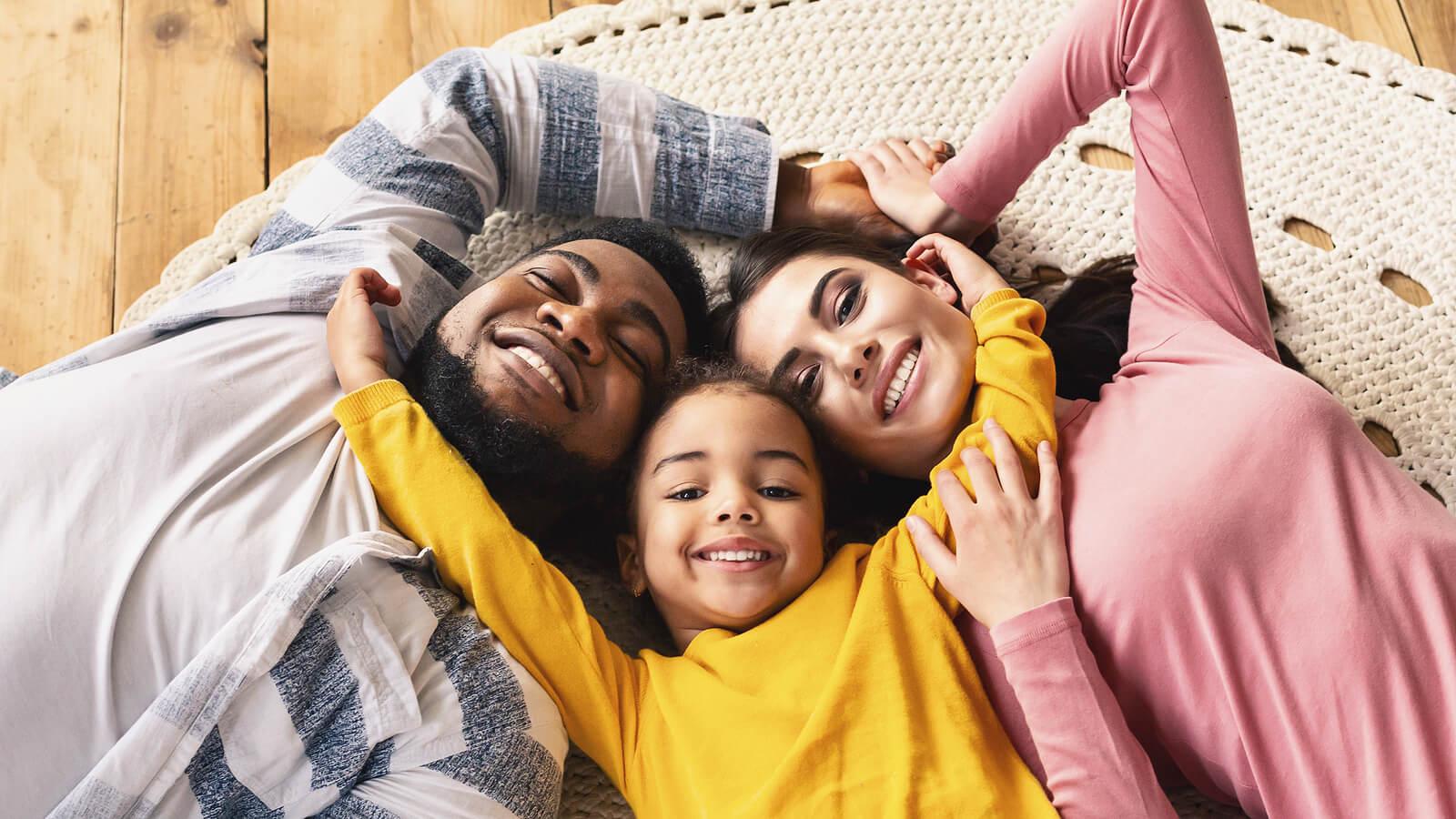 Familia feliz tumbada en el suelo mientras se dan un abrazo para practicar la crianza conectada.