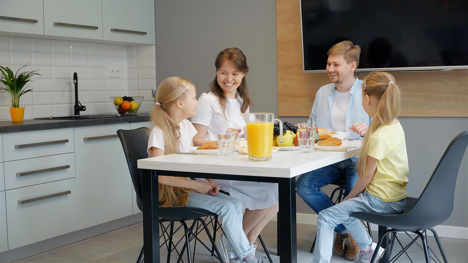Padres desayunando junto a sus hijas.