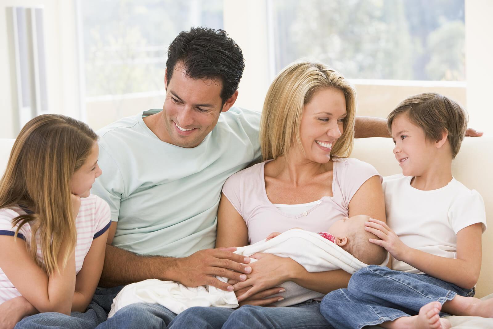 Familia con sus hijos y con su bebé recién nacido en brazos.