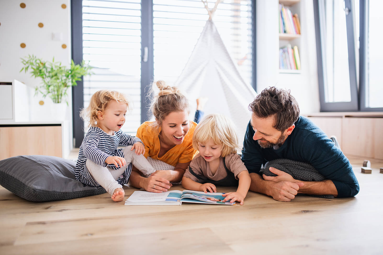 Familia leyendo cuentos breves con valores tumbados en el suelo.