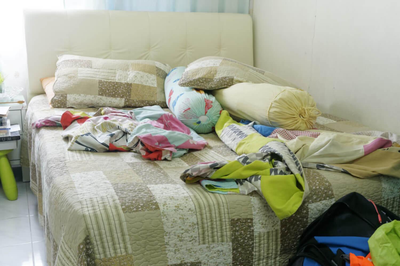 Cama llena de ropa y desordenada.