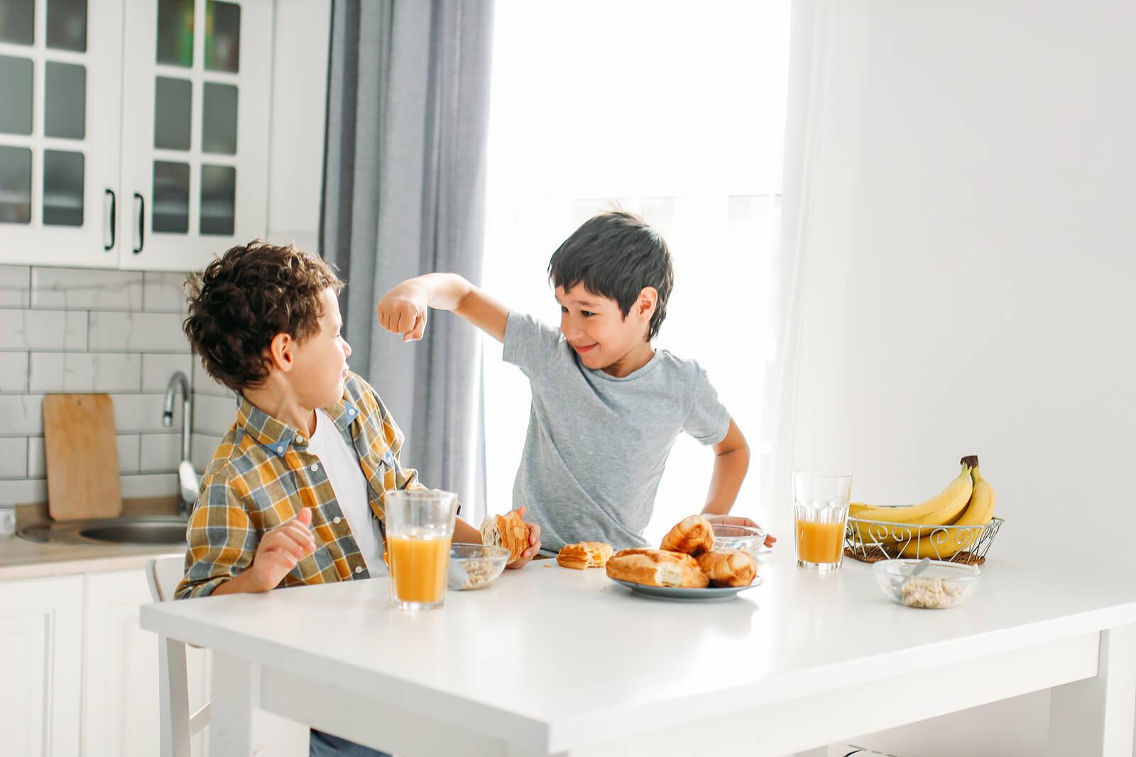 Hermanos peleándose durante el desayuno.