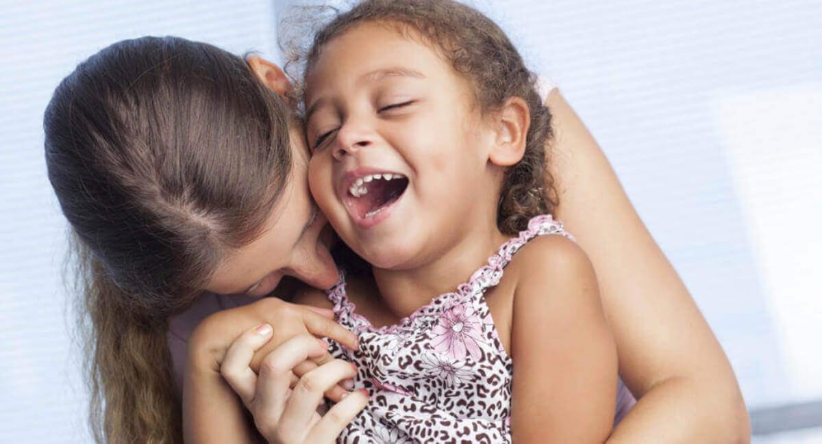 Madre dando un beso a su hija en la mejilla.