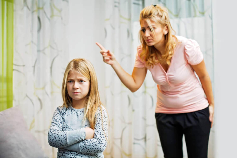 Madre con el dedo levantado castigando a su hija.