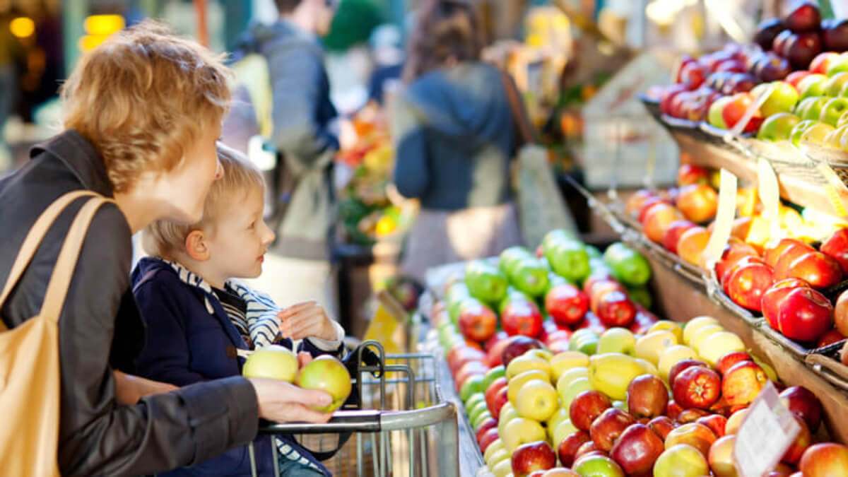 Madre con su hijo en el supermercado comprando.