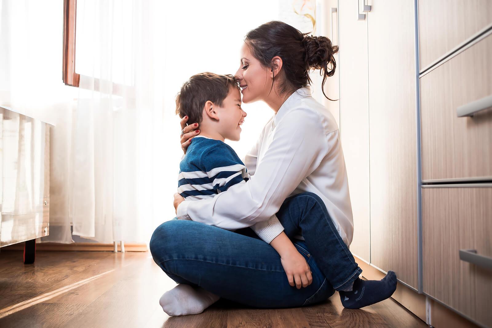 Madre dando un abrazo y un beso en la frente a su hijo gracias a la crianza conectada.