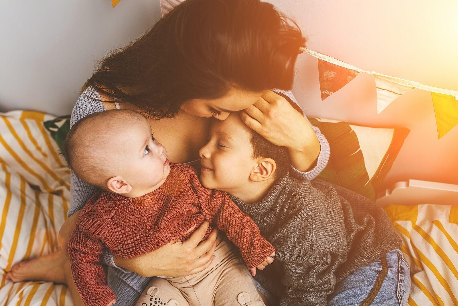 Madre dando besos y abrazos a sus hijos.