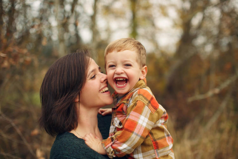 Madre dando un beso y un abrazo a su hijo.
