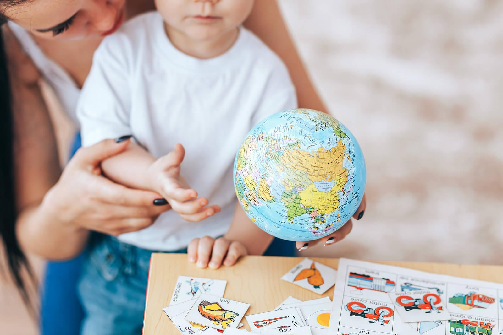 Los padres atentos son la clave del éxito de los hijos, como esta madre con su pequeño y la bola del mundo.