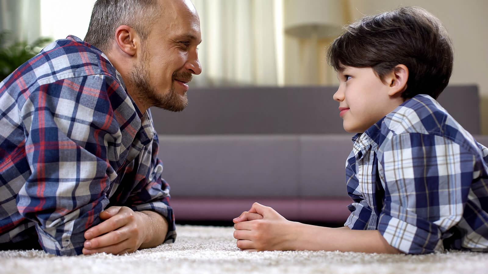 Padre hablando con su hijo sobre el contrato de contingencias para la modificar su conducta.