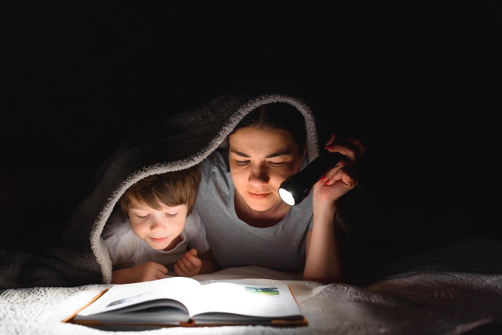 Madre con su hijo leyendo un cuento a la luz de la linterna mientras se tapan con las sábanas de la cama.