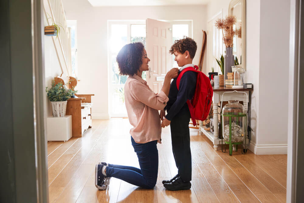 Madre preparando a su hijo para ir al cole.