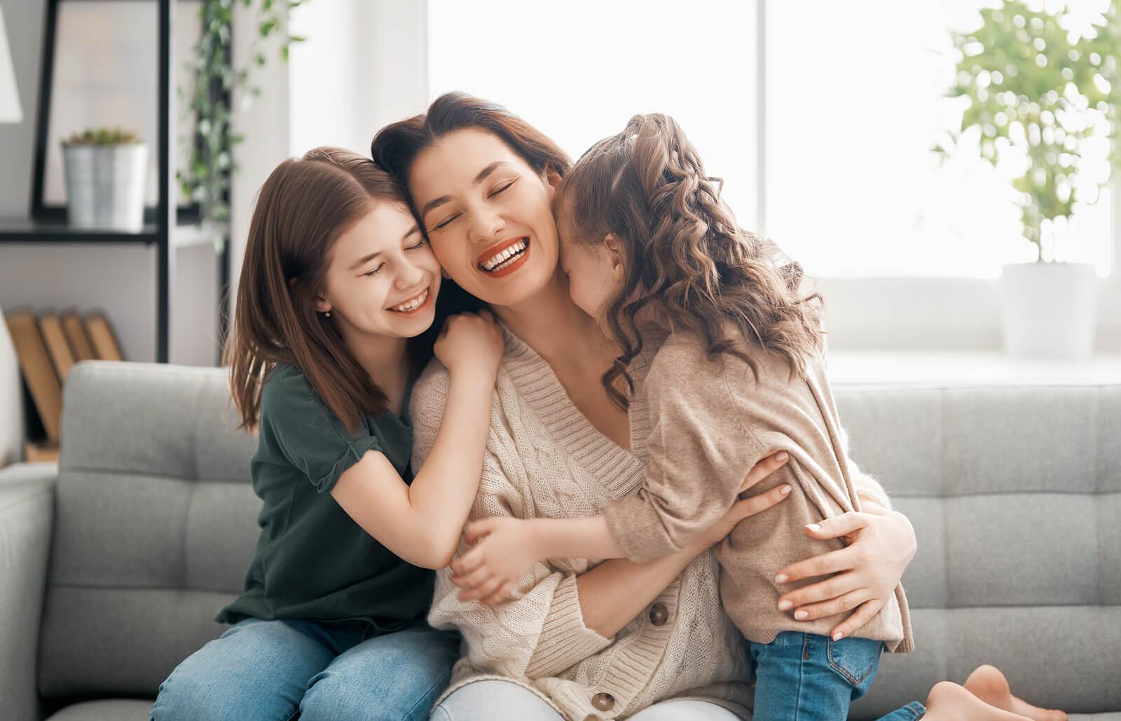 Madre abrazando a sus hijas porque es el tipo de mamá completa.