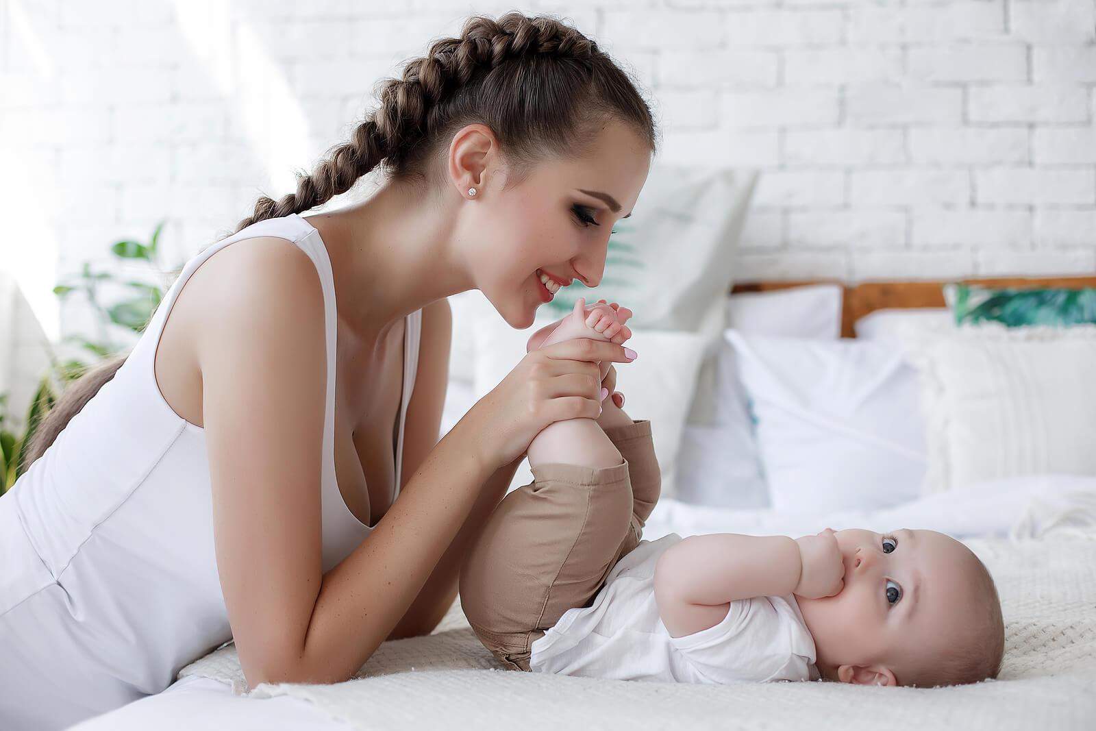 Mamá jugando con sus bebé para cubrir sus necesidades emocionales.