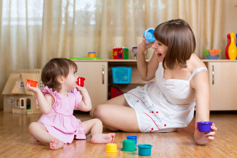 Mamá jugando con su bebé para el desarrollo de la motricidad fina y gruesa.