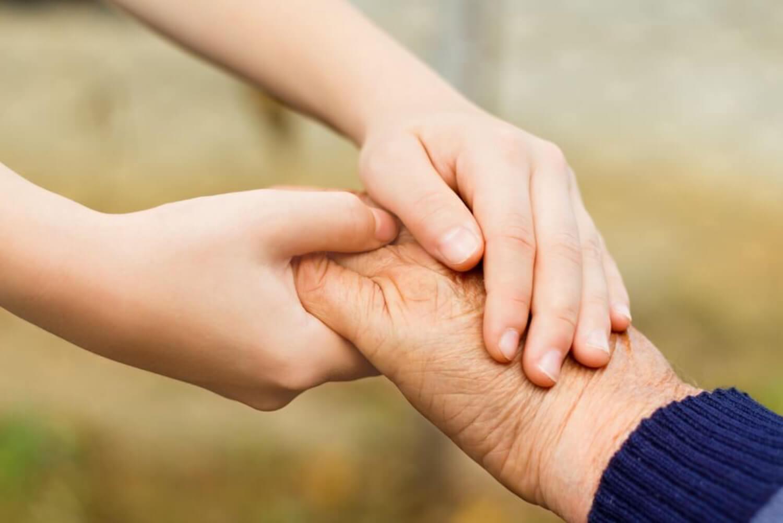 Nieto dándole la mano a su abuelo.
