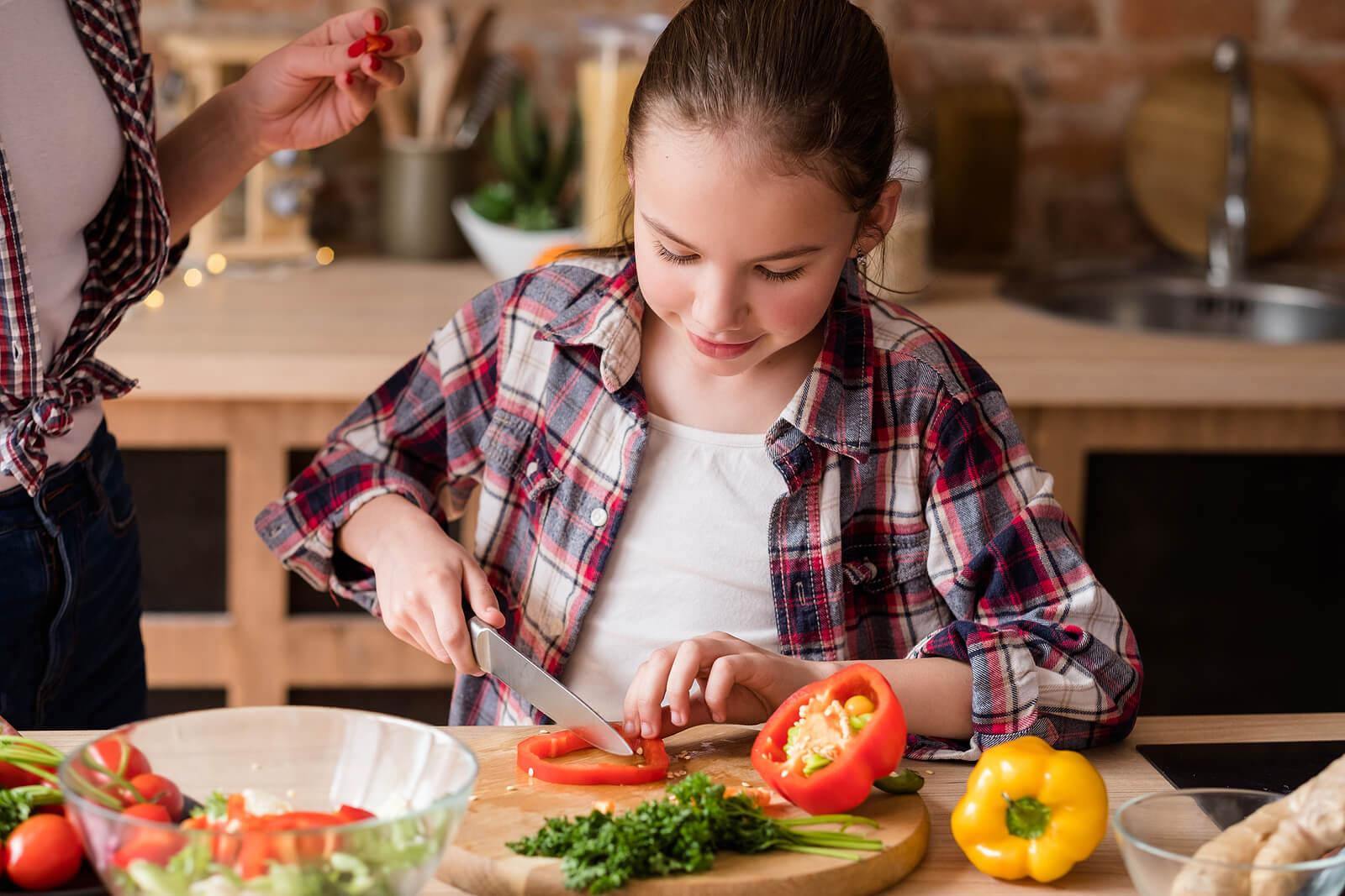 Niña ayudando en la cocina para aumentar el consumo de verduras.