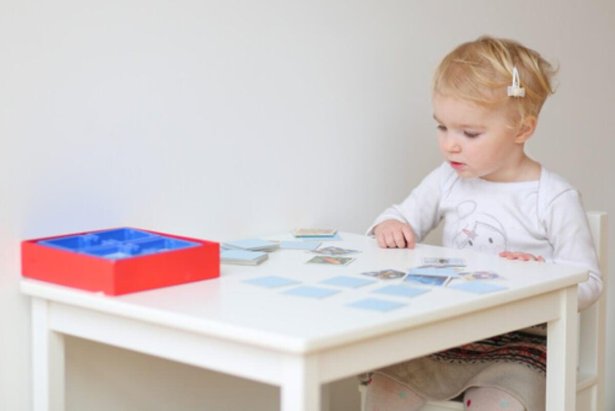 Niña jugando a juegos de cartas para desarrollar la memoria funcional.