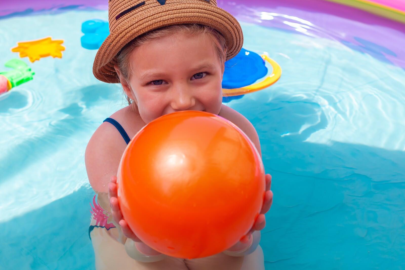 Niña con un globo de agua en una de las piscinas hinchables.