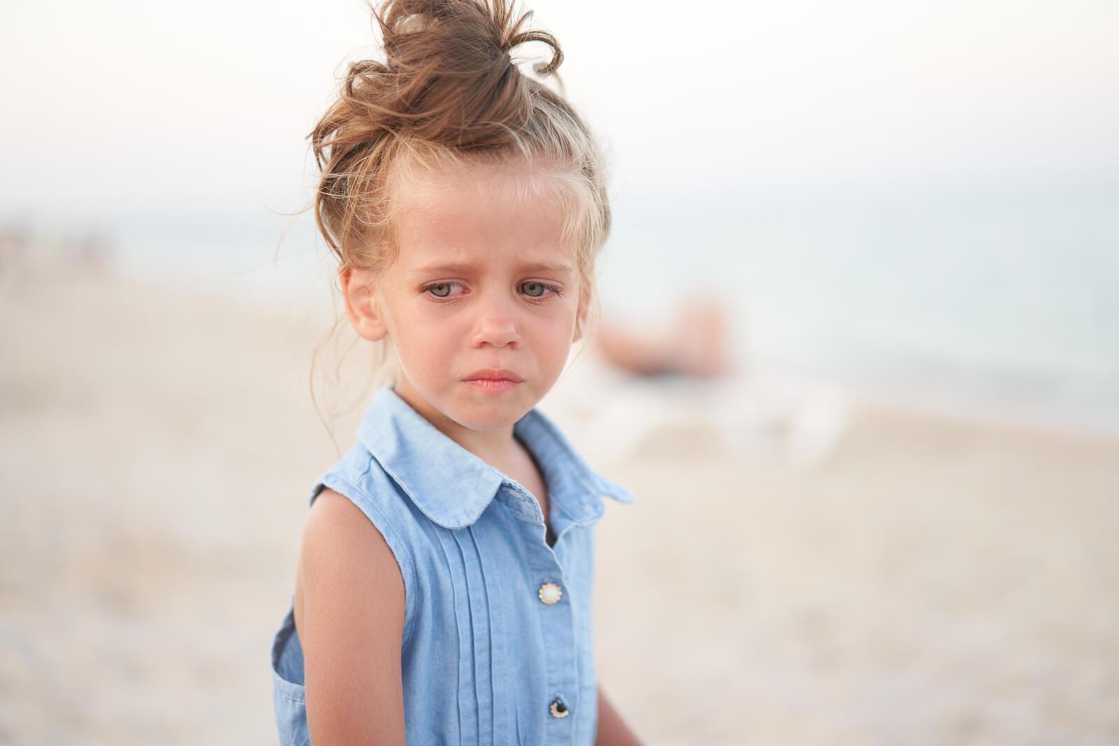 Niña llorando en la playa porque a sus padres les cuesta reconocer cuando un niño está triste.