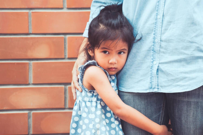 Niña con miedo abrazada a la pierna de su padre.