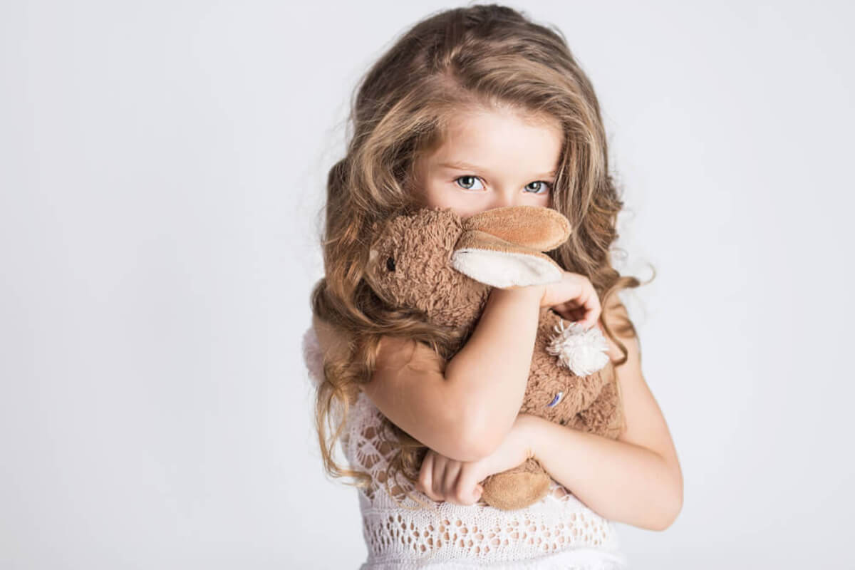 Niña vergonzosa abrazando su conejo de peluche.