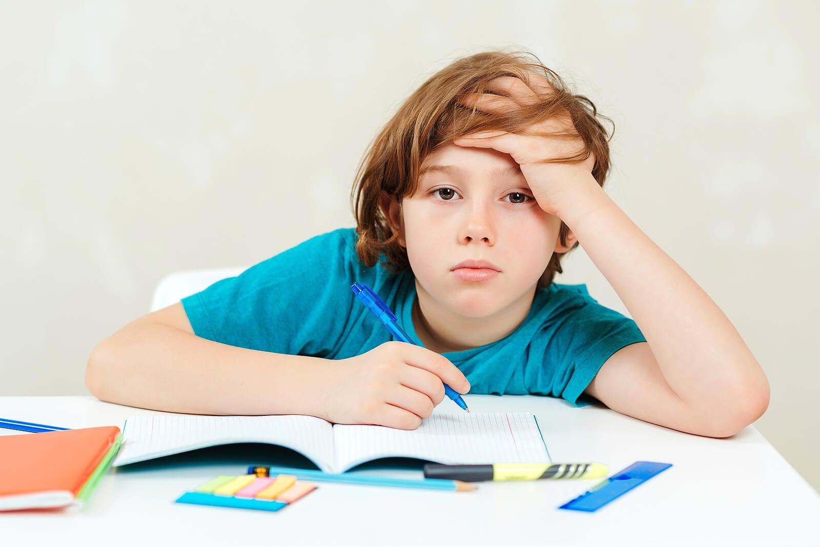 Niño aburrido porque sus padres no saben cómo motivar a los niños a hacer los deberes.