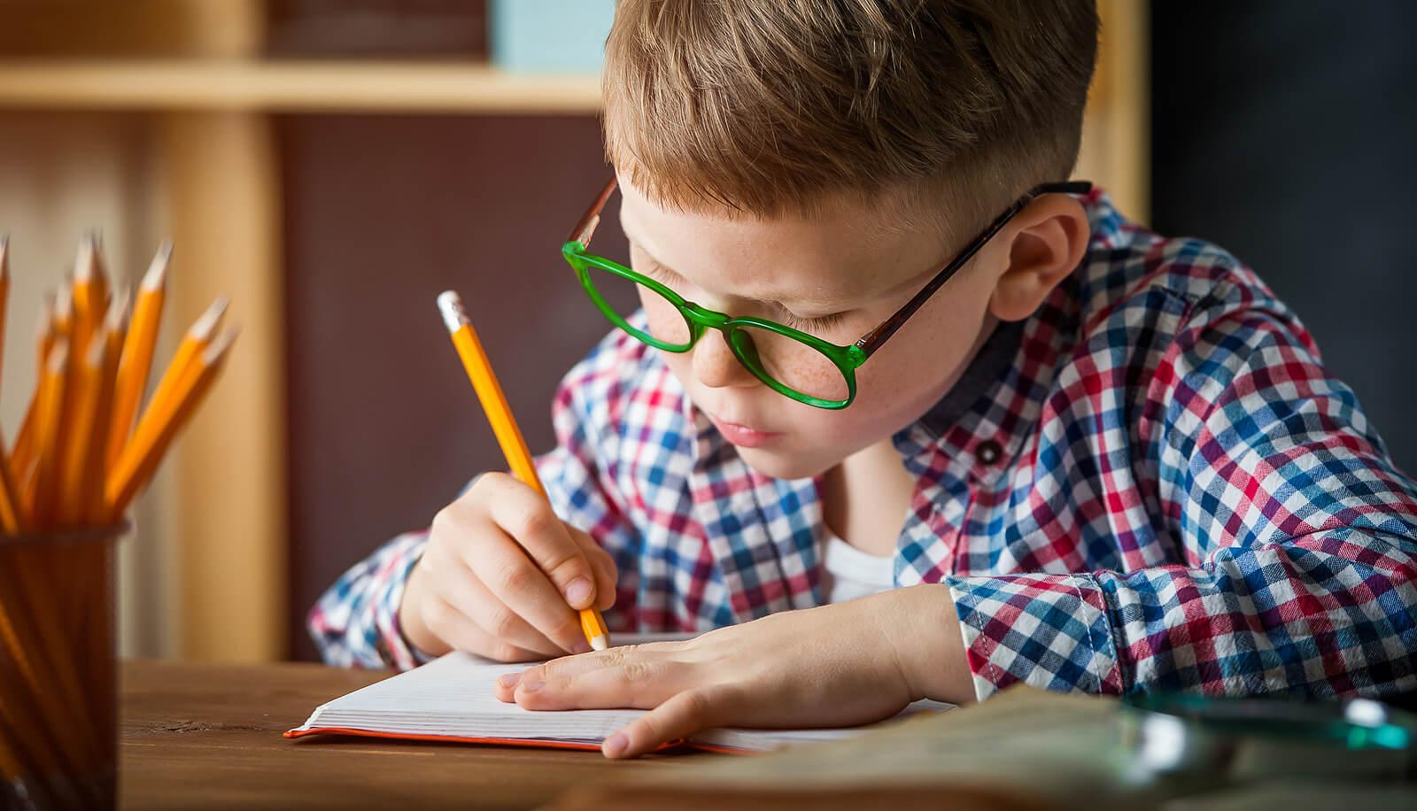 """Niño escribiendo en su """"lista feliz"""" todo aquello por lo que está agradecido."""