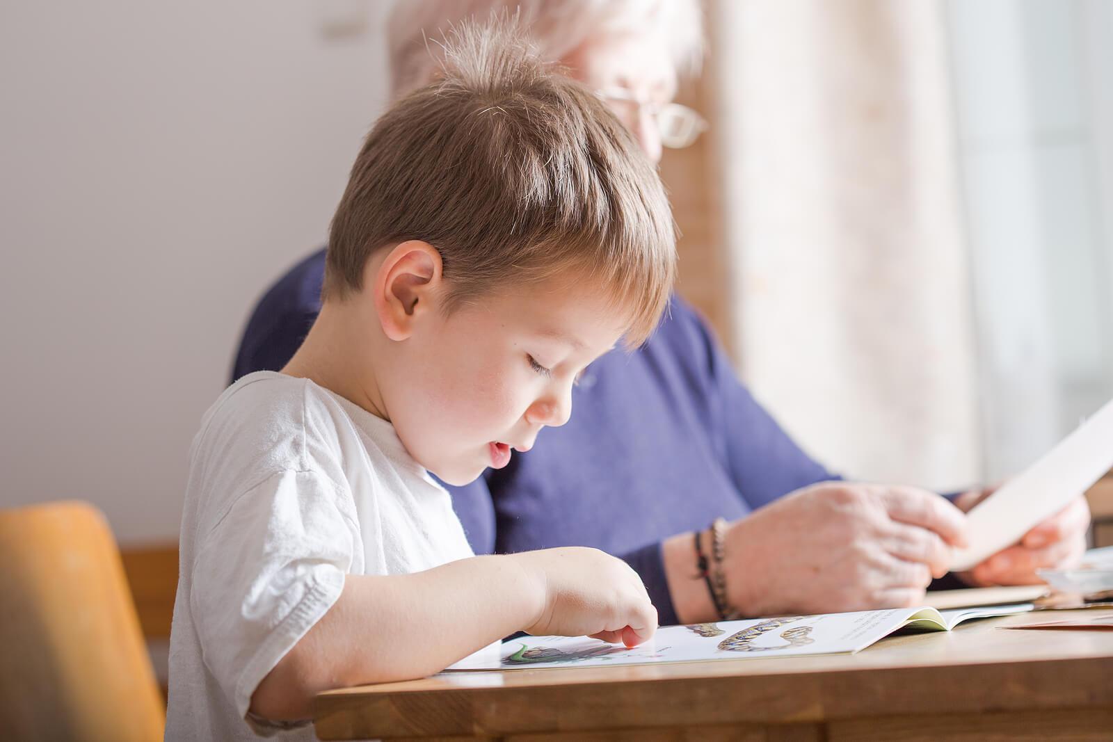 Niño aprendiendo a leer gracias a las ideas para fomentar la lectoescritura.