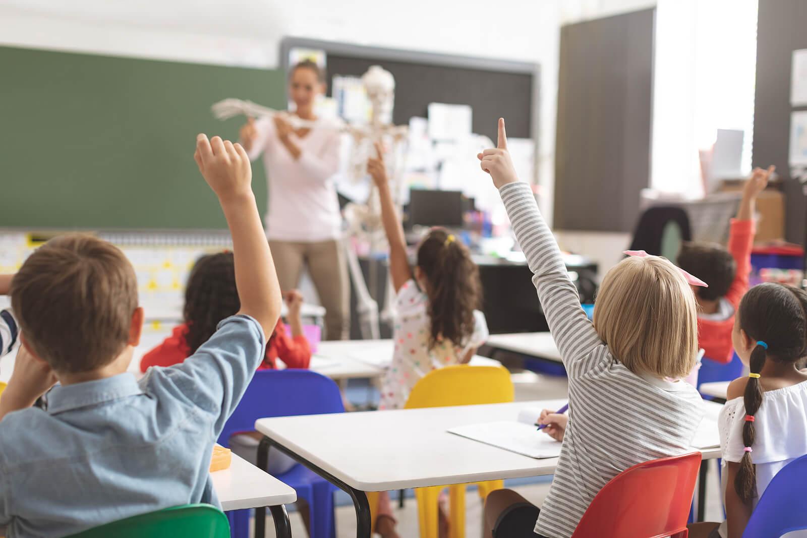 Profesora en clase con sus alumnos aplicando estrategias para fomentar la resiliencia en el aula.