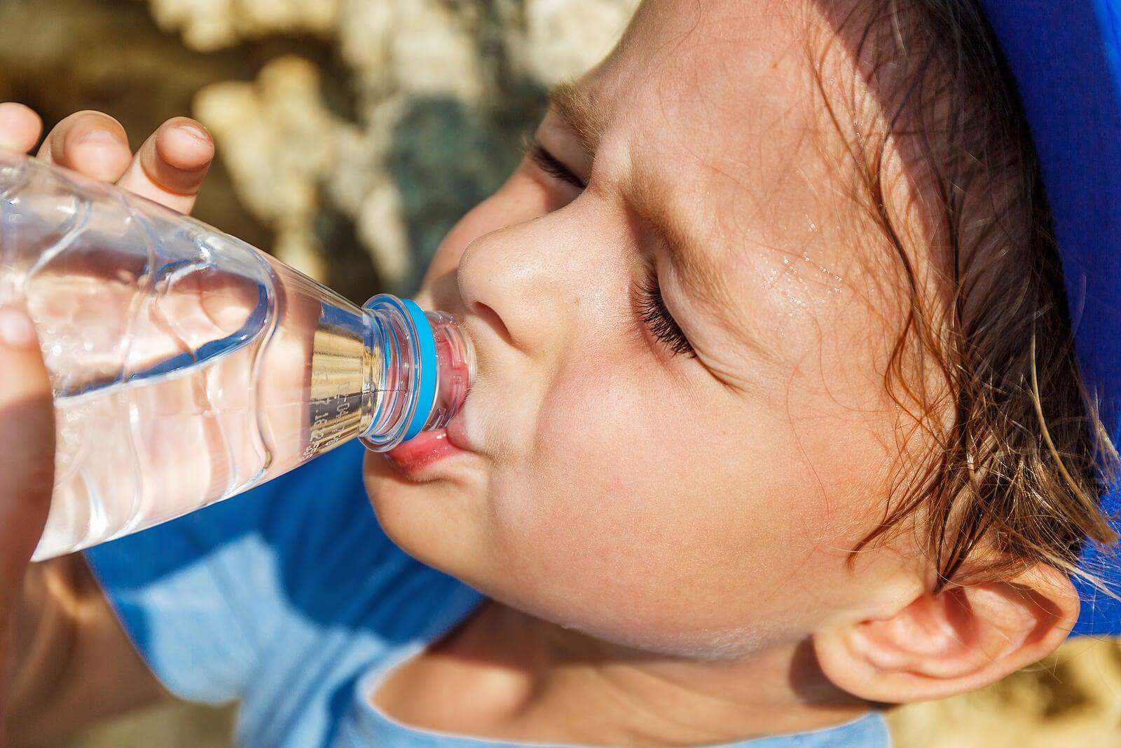 Niño bebiendo agua porque suda mucho.