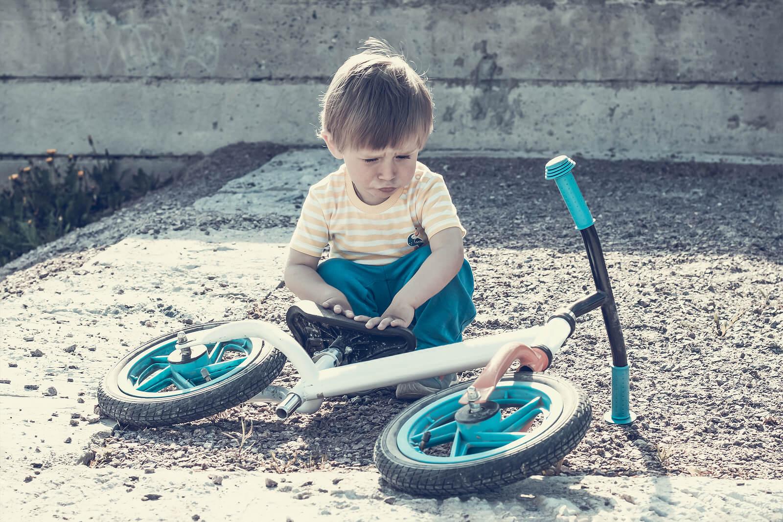 Niño de 2 años con la bicicleta tirada por el suelo.
