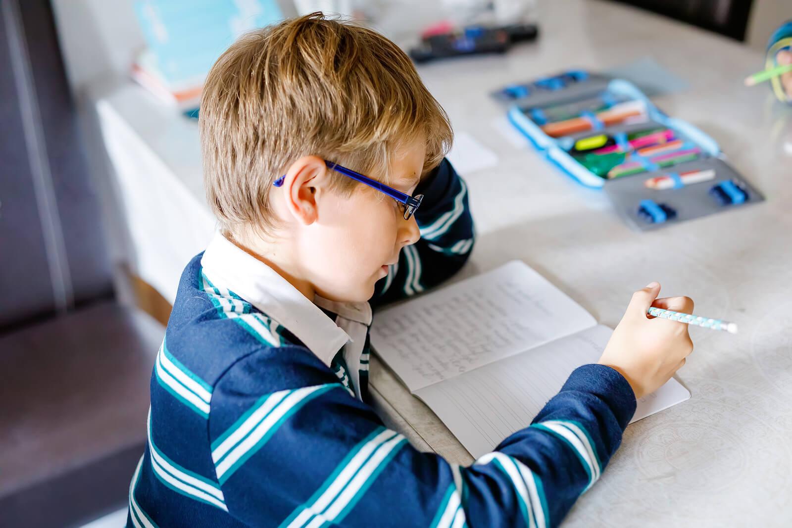 Niño escribiendo una historia para su taller de escritura creativa.