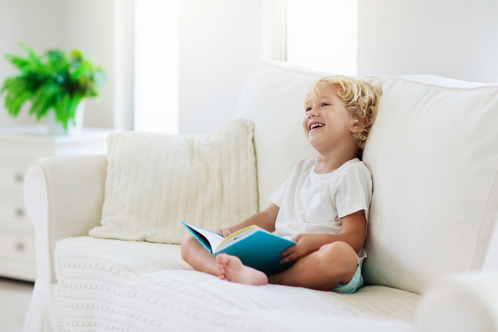 Niño leyendo cuentos sobre la envidia sentado en el sofá de casa.