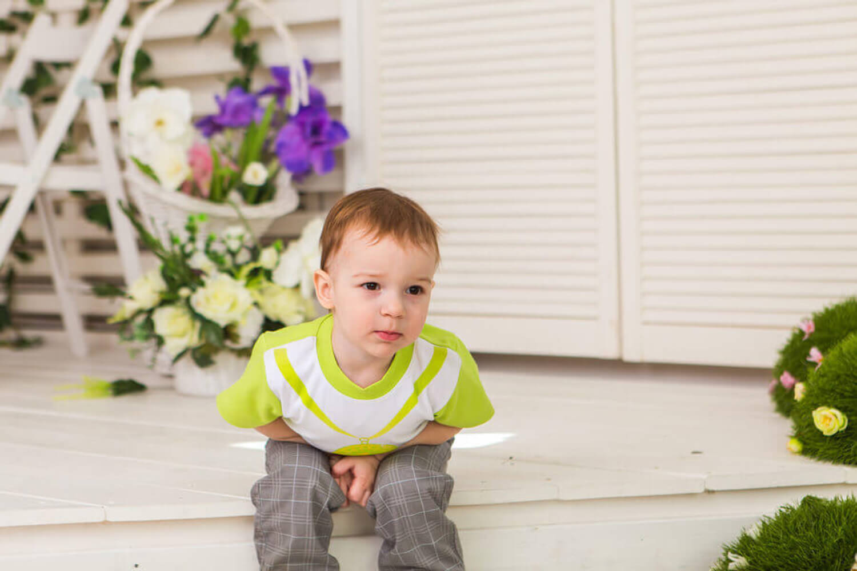 Niño con dolor de barriga sentado en un escalón.