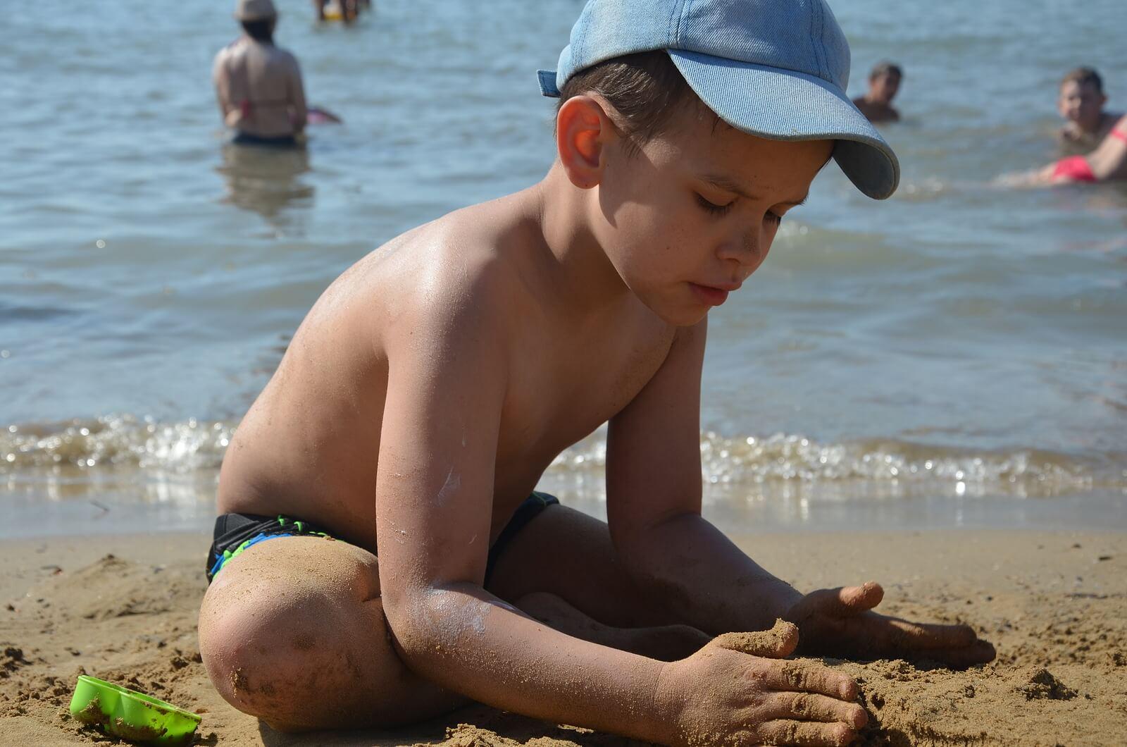 Niño en la playa haciendo un castillo de arena con la vigilancia de sus padres para evitar el ahogamiento en niños.