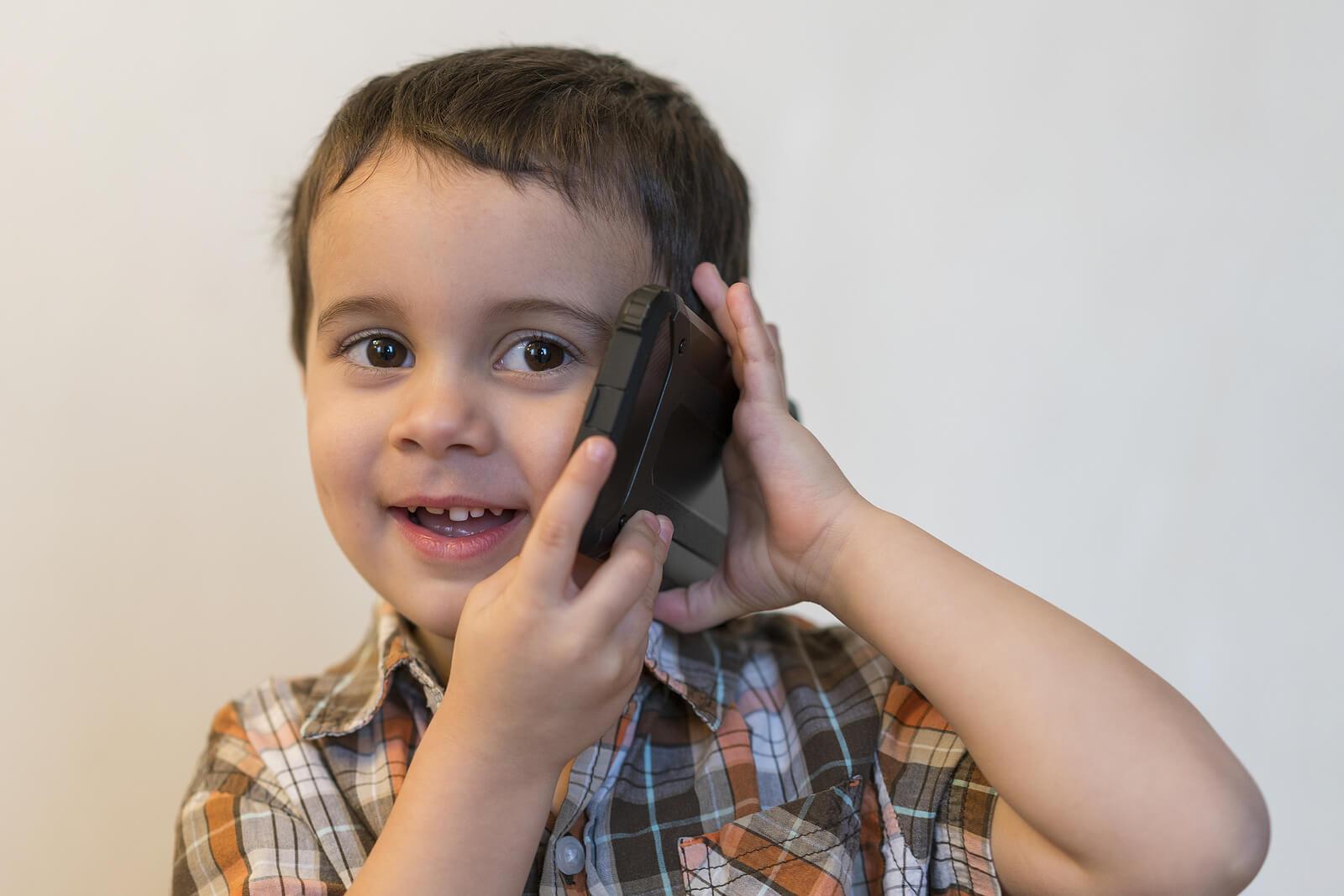 Niño de tres años hablando por teléfono.