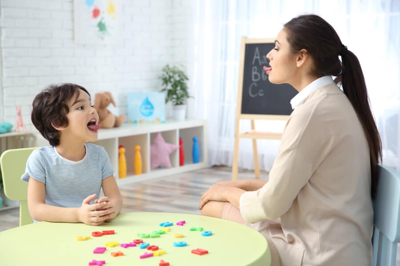 Niño en sus sesión de logopedia haciendo ejercicios con la lengua.